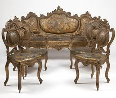 Italian Rococo Style Giltwood Parlor Suite. Mid 19th century, comprising a settee, two armchairs and two side chairs,the frames elaborately carved with foliate scrolls and rocaille, upholstered with gilt and polychromed stamped leather depicting cherubs and floral trophies within foliate scroll borders.