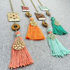 Choose 1 from 4 Colors Funky Trendy Boho Tassel charm necklace with a textile ribbon Detail.  These necklaces are full of fun will infuse your outfit with the right amount of boho flair.They can be either worn by themselves of layered with necklaces of your choice. Each necklace comprises of a handmade pure cotton tassel with a dull gold plated brass charm a wood donut bead and a co-ordinated strip of fabric/textile ribbon. The chain is dull gold plated metal. Length: 14 Length of ribbon...