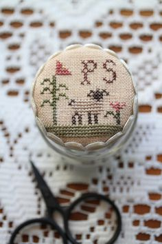 from Plum Street Samplers; stitch a small design. cut in a circle and stretch over the top of a pimento jar lid (with a small piece of thin batting underneath the stitched piece). Then add mother-of-pearl hex buttons on the sides. (I can't find this on the blog - will have to search!)
