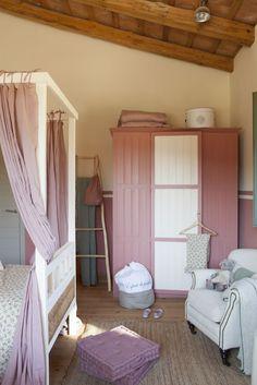 00382546 O. armario pintado en blanco y rosa en un dormitorio rustico