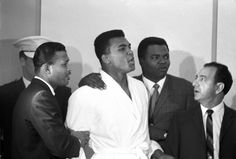 Muhammad Ali (then known as Cassius Clay ) is held by Sugar Ray Robinson (left) and Bundini Brown while taunting Sonny Liston before the weigh-in of their World Heavyweight Title fight at the Cypress Room of the Miami Beach Convention Hall. Neil Leifer, Dr Ali, Sugar Ray Robinson, Muhammad Ali Boxing, Laila Ali, Black King And Queen, Leroy Neiman, Boxing, Sports