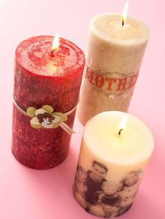 Print photos or digital designs onto tissue paper and cut out the images. Wrap the candles with the tissue paper and keep it in place with straight pins. A heat gun will melt the wax until it saturates and coats the tissue paper. A hidden brad embedded in the candle secures the flowers.