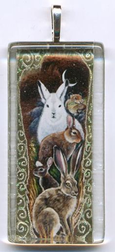 Miniaturized image of my feather painting, Hare Totem. Hand-tinted with gel pens and mounted on the back of a tempered glass tile. Attached bail