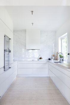Kjøkkenet er åpnet ut mot spisestuen og holdt like lyst og luftig som resten av huset. Innredningen er fra HTH, men det vakreste er nok den heldekkende marmorveggen. Flaten er kun brutt av viften fra Røros Metall, som er blitt spraylakkert i klassisk hvit, fargen som går igjen på alle flater.