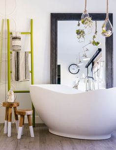 We love how the Signature Hardware freestanding tub looks in this contemporary bathroom in front of this floor mirror and under these hanging plants.The elegant sloping walls of the tub will bring a refined and eclectic style to your space. Bathroom Photos, Bathrooms, Bathroom Ideas, Bathroom Mirrors, Bathroom Remodeling, Master Bathroom, Open Door Policy, Bathtub Decor, Luxury Mirror