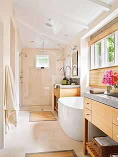 Natural color oak and neutral limestone keep the palette in this bathroom light. At the end of the room is the expansive shower. Often shower glass can appear green, but these homeowners chose a special glass without color distortion, so the shower practically disappears.