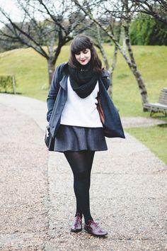 Look confortável de Inverno. Melina Souza com saia de lã cinza escuro, tricô branco, casaco xadrez acinturado, meia-calça preta, oxford borgonha com verniz e bolsa preta com detalhes dourados.