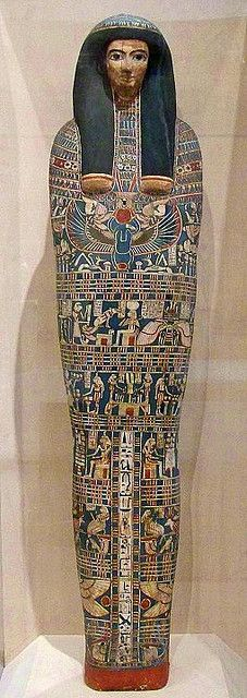 "Mummy case, c. 800 BCE (Dynasty 22). The name ""Ankh-Tesh"" is written at the bottom of the column of hieroglyphs.  Ankh-Tesh is shown with the gold skin of the deified dead. Water lilies, symbolizing the daily rebirth of the sun, crown her heavy wig. A collar of flowers covers her shoulders, and a black metal scarab hangs from a ribbon. Her crossed hands grip protective amulets. The painted scenes represent gods and events as Ankh-Tesh enters the next life."