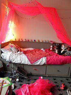 Un lit de petite fille avec ciel de lit rose fluo, il fallait oser !