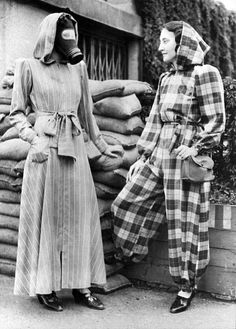 London, England Sept 14, 1939.The very latest fashion in air raid shelter wear is a slip on dressing gown complete with hood, and can be left open, (left), or zipped into trousers, (right).