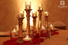 A classic look featuring high and low gold candlesticks, with a candle river surrounded by red rose petals.  Reception & Wedding Centerpieces   Occasions by Shangril-La