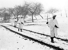 Three members of an American patrol cross a snow covered Luxembourg field near Lellig on a scouting mission. White bedsheets camouflage them in the snow, December 30, 1944. Left to right: Sgt. James Storey, Newman, Ga.; Pvt. Frank A. Fox, Wilmington, Del., and Cpl. Dennis Lavanoha, Harrisville, N.Y.