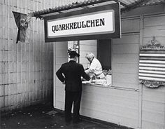 Street kitchen, East Berlin, 1961. 'Quarkkäulchen' are pancakes made from dough containing mashed potatoes, quark cheese, eggs and flour, sometimes spiced with cinnamon or dotted with raisins. They are served hot with sugar and fruits, or other sweet side dishes. (Sounds good.)