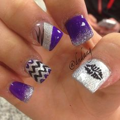 Silver glitter nail art with black and violet polish in stripes and zigzag details.