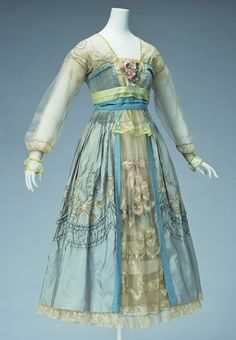 Evening Dress  1916 Lucy Christina Wallace Dress characterized by palecolouringand delicate decoration. The skirt section isthree-layered, with the front opening of the overskirt giving glimpses of a large number of decorations in tulle and lace patched together, with silk satin ribbons and flowers.  As a result of World War I, fashion turned rapidly in the direction of simplicity. However, many women still longed for the decorative, traditional styles, providing a clientele for Lanvin…