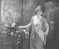 c.1921 Baron de Meyer ,Actress Mary Young   Actress Mary Young wearing a Georgette crepe tea gown decorated with bands of silver embroidery on the sleeves, designed by Lucile.