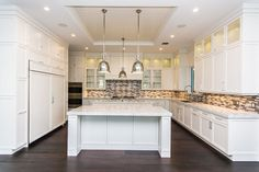 Beautiful contemporary kitchen with white cabinets backsplash wood floor marble island