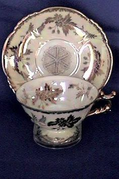 A post-war china teacup and saucer from Japan with lots of hand painted and hand decorated work. This set has an irridized finish over white porcelain with an all-over 24k gold decoration. A beautiful example of Japanese workmanship.