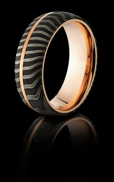 Hand made tiger patterned Damascus steel ring with a 14k rose gold sleeve and inlay.