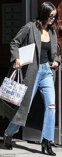 Prepared: A white book tucked under her arm and a colorful bag in her hand, Selena balanced on a pair of gleaming black high-heeled boots
