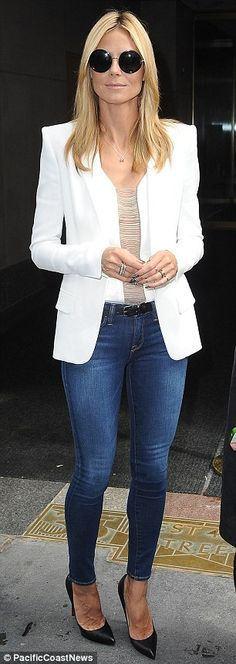Putting her best foot forward: The German beauty displayed her enviably long, lean legs in a pair of skintight jeans, paired with a thin black belt, matching pointy stilettos, a white top featuring a risqué vertical draped sheer panel down the centre and a crisp white blazer with padded shoulder detail