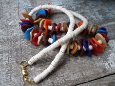 This very colorful necklace has been made from many polymer clay discs and creamy colored heshi wood beads for a very bohemian feel.