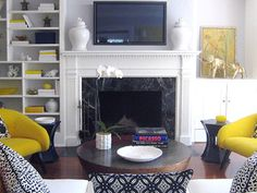 How to decorate around a TV without making it the focal point in the room....  using color and asymmetry to create interest elsewhere and make the TV blend in, instead of standing out.