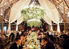 Wagon Wheel Florals/greenery in-between chandeliers and drapery.