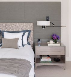modern master bedroom : great, minimal color scheme : feature wall : layered headboard : bedding : nightstand : mounted light fixture