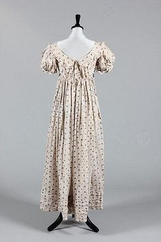 A cotton printed cotton day dress, circa 1820, roller-printed with teal-blue flowerheads and wine scrolling grasses, empire line with puff sleeves, flounces to neck and cuffs, piped bands to hem