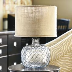 "Emmett Table Lamp:  Why stop with storage baskets? We love the look of French wire so much we added it to a lamp. The clear glass lamp base is hand finished in twisted black wire for stylish contrast and vintage texture. Lamp comes with a 14"" Burlap Drum Shade."
