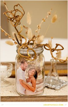 Use mason jars as picture frames for your centerpieces. Wedding Decorations! DIY photo by www.adamplusalli.com