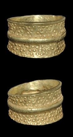 Viking gold Ring with punched triangles, 10th-11th century. A cast finger ring with expanding hoop and raised median band, the outer face impressed with punchmarks, each a triangle with pellets in the corners.