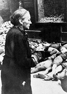 Outubro de 1944, uma mulher idosa olha para as crianças mortas fora de uma escola em Braunschweig após um bombardeio dos Aliados. Bundesarchiv Bild