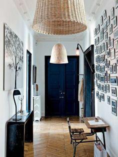Luminaires couloir. Porte couleur bleu fonce. Un tableau avec un arbre est pendu sur le mur.