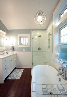 A modestly sized bathroom with a clawfoot bathtub, a small crystal chandelier, and classic white subway tile.