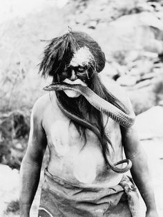 Hopi Indian with painted face and body and snake in mouth. Photo by Ralph Murphy, 1924.