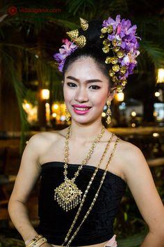 Dançarina tailandesa em roupas tradicionais posa para foto. Veste blusa preta, cordões dourados e ornamentos de cabeça floridos.