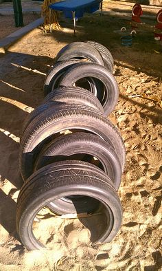 Tires in the playground- I could make use of all Hunter's tires behind the shed! HA!