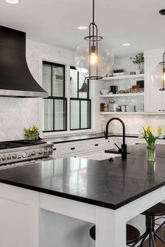 A simple design using white cabinets along with black countertop backsplash coveys a bold yet inexpensive and vibrant kitchen. Black Kitchen Countertops, Countertop Backsplash, Dark Kitchen Cabinets, Black Quartz Countertops, Modern Countertops, White Cabinets White Countertops, Black Countertops White Cabinets, Kitchen Cabinets Black And White, White Cabinet Kitchen