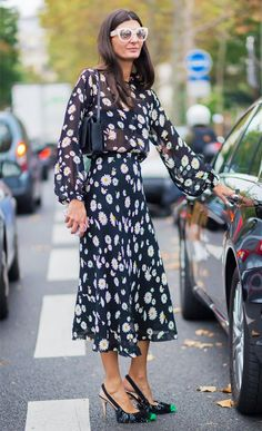 A sheer floral dress is worn with a black bag and spiked pumps