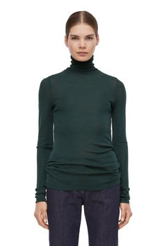 This jersey roll-neck top is knit from pure merino wool. Its sheer quality and slim elongated fit make it suitable for layering. The material reacts to bod