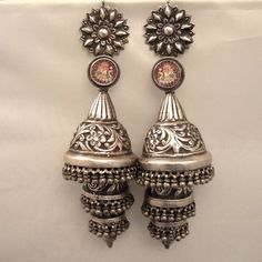 """Silver, India Description A pair of earrings unique antique from the Rajasthan called """"phuljhumka"""" and worn by Gypsy Lambadi or benjara nomads: in this case, 3 floors, floral designs are truly amazing ... these earrings are dedicated to Ganesh as shown in the small thumbnails under glass in the upper loops ... therefore their weight and size make parts for discerning collectors ... Weight: 99.85 gr ET102, 70 gr"""