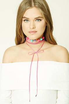 A velvet choker featuring a layered design, multicolored pom pom accents, self-tie front closure, and high-polish ends.
