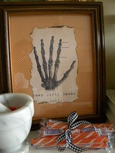(maybe for mantle or long table, frame pages from anatomy book, that have been dipped in green/black tea/rubbed with tea soaked cotton ball to age slightly along with being crumbled and torn, then have cotton webs strewn over and around, along with candles and skulls and other decorations.)