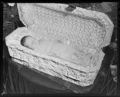 Post-mortem image of baby wearing sweater in casket, 1949.