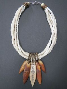 Necklace   Luda Hunter.   5 strands of shell heishi and rondelle beads, combined with 5 Ethiopian bone spear pendants that are attached with small Nepalese brass beads