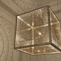 Crossing Boundaries by Anila Quayyum Agha. Laser cut panels surround a light bulb casting stunning patterned shadows.
