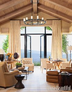 With a breathtaking view of the coastal California countryside, this living room is an ideal spot to entertain. The multiple seating areas accommodate either a large or small crowd. Designer Suzanne Tucker chose warm colors for a cozy feel even on a foggy day.   - HouseBeautiful.com