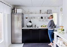 Keittiöstä tuli valoisa ja avara, kun turhat seinät purettiin. Hannele halusi mökille vain kaikkein tarpeellisimmat esineet. Niistä kauneimmat saavat olla esillä. Kompakti keittiö sopii pariskunnan tarpeisiin mainiosti.